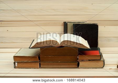 Pile of books. Open book hardback books on wooden table. Knowledge is important. Copy space.