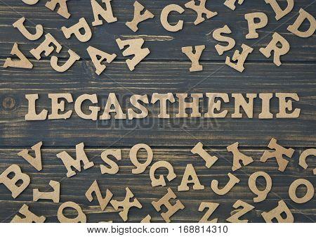 Word legasthenie on a dark wooden background