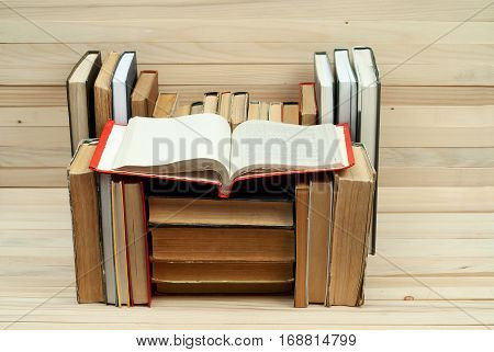 Old and used hardback books or text books on wooden table. Books and reading are essential for self improvement gaining knowledge and success in our careers business and personal lives.