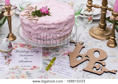 Pink wedding cake with rose on the top and lettering Love. Text of invitation card:
