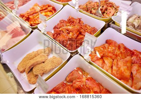 sale and food concept - marinated meat in bowls at grocery stall