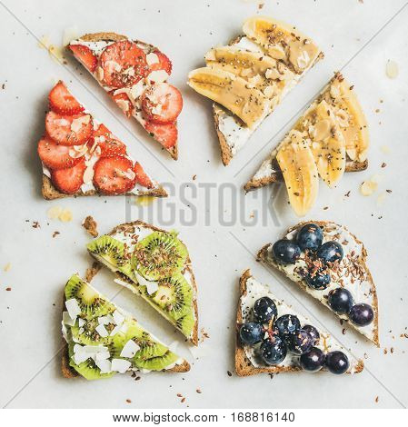 Healthy breakfast toasts cut in pieces. Wholegrain bread slices with cream cheese, various fruit, seeds and nuts. Top view, grey marble background, square crop. Clean eating, vegetarian concept