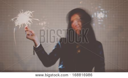 Blurred in motion image of young woman dancing with burning sparkler in her hands in the night city street, retro color, colorized image.