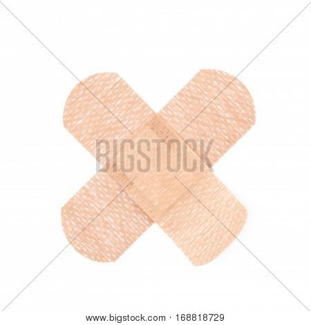 Cross shaped adhesive bandage sticking plaster isolated over the white background