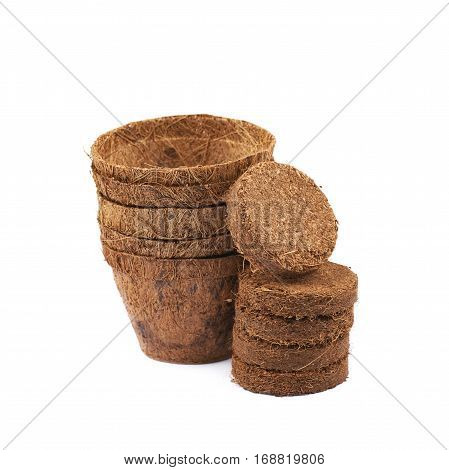 Degradable coconut pot next to a pile of compressed compost tablets, composition isolated over the white background