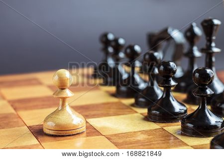 One pawn staying against full set of black chess pieces. With selective focus on pawn.