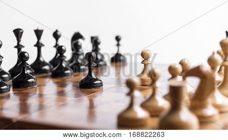 Pawns staying against full set of chess pieces. With selective focus on pawn.