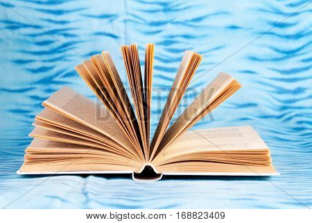 Old and used hardback books or text books on wooden table. Books and reading are essential for self improvement gaining knowledge and success in our careers business and personal lives. Copy space.