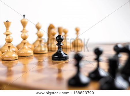 One pawn staying against full set of white chess pieces. With selective focus on pawn.
