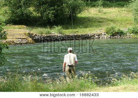 standing in the river fisher man with fishing stick