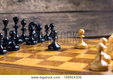 One pawns staying against full set of chess pieces. With selective focus on pawn.