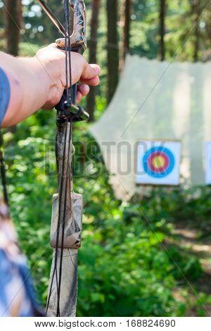 Man aiming bow at target outdoors