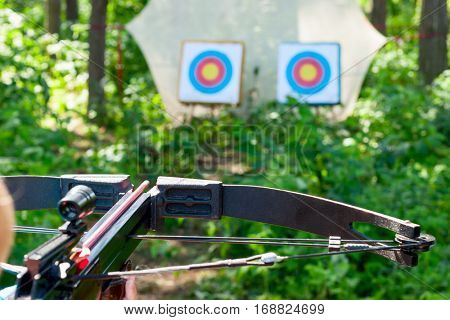 Woman aiming crossbow at target outdoor