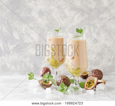 pink milkshake with ice cubes and mint leaves and fruits of passion fruit on a marble table, selective focus, high resolution