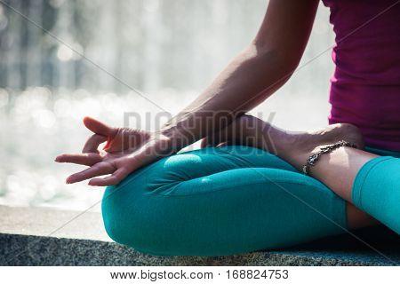 woman hand closeup in lotus yoga position outdoor shot