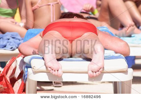 Adult woman on a deckchair having sunbathe - close up