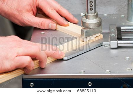 Craftsman working on frame in frame shop. Professional framer hand holding frame angle. Top view. poster