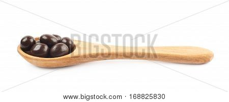 Wooden spoon full of chocolate ball candies isolated over the white background