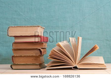 Open book stack of hardback books on table. Back to school. Copy space.