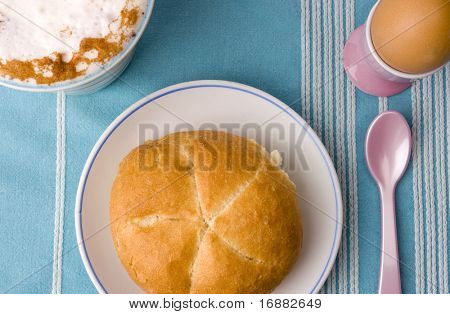 breakfast - cup of cappuccino, boiled egg in cup with spoon and roll on the plate on table-cloth