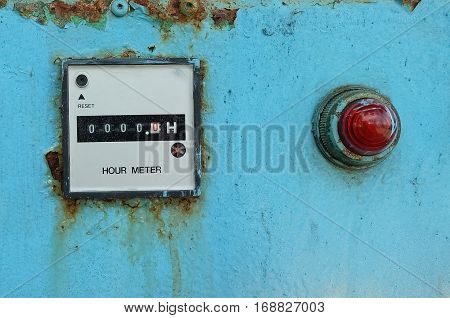 Old Electric Meter Measurement Tool with Alarm Light on The Blue Metal Grunge Wall.