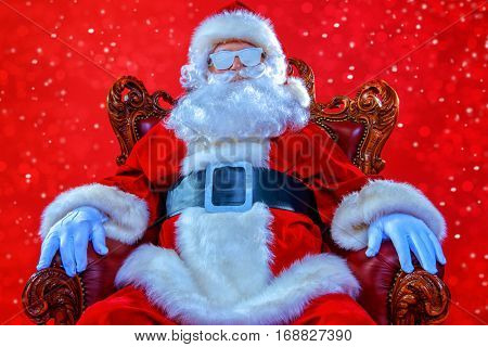 Portrait of cool modern Santa Claus wearing snow covered sunglasses over red background. Christmas concept.