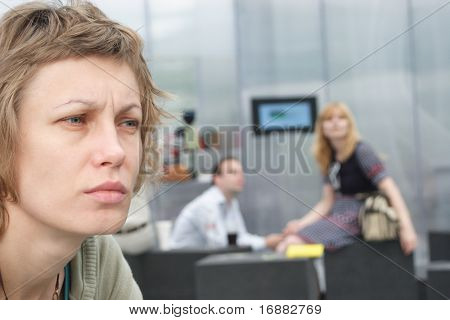 Sad woman with couple in background - out of focus