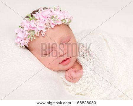 cute newborn baby in headband with flowers smiling asleep, closeup