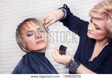 Women's haircut. Hairdresser, beauty salon. Professional hairdresser making stylish haircut. Hairdresser middle aged woman cutting bangs hair. Stylist holding comb and scissors