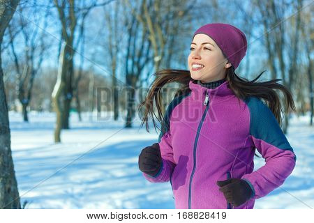 Running sport woman. Female runner jogging in cold winter forest wearing warm sporty running clothing and gloves. Fitness happy girl running in winter park. Fitness and healthy lifestyle concept