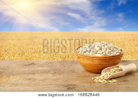 Oat flakes in bowl. Grains of oat in scoop and oatmeal in bowl on wooden table with field on the background. Ripe field, blue sky with beautiful clouds and sun. Uncooked porridge