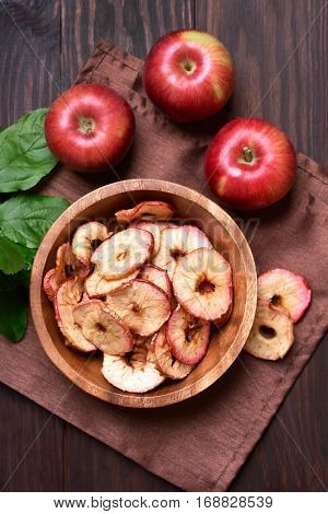 Healthy snack dehydrated apples chips in wooden bowl top view