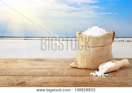 sea salt in bag. Crystals of salt in sack on table with salty lake with sun in the background. Bag of sea salt produced on farm