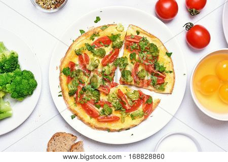 Omelette with broccoli tomato and green herbs top view.