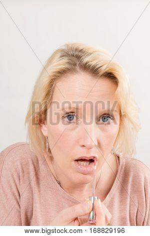 Woman Applying Gloss On Lips Direct Gaze With Copy Space