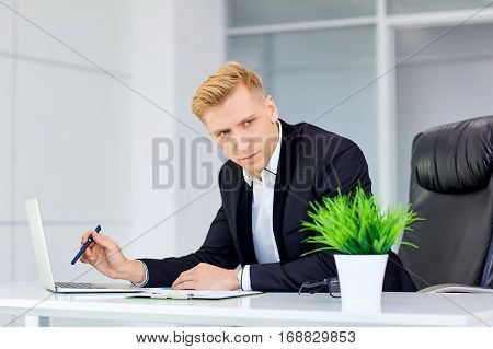 Serious blonde man is thinking in front a laptop at his desk the office workplace.