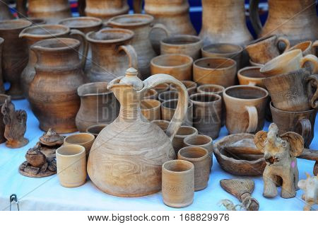 Close up on Traditional Ceramic Jugs on Decorative Towel. Showcase of Handmade Ukraine Ceramic Pottery in a Roadside Market with Ceramic Pots and Clay Plates Outdoors.