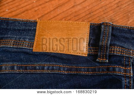 Details from back blue jeans closeup-wooden background