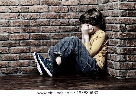 Portrait of a sad nine year old boy sitting in the corner with his face in his hands.