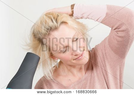 Woman With Eyes Closed While Drying Hair With Blow Dryer