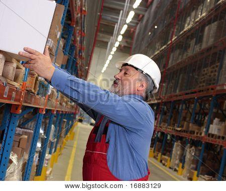 older worker in uniform putting box on shelf in warehouse