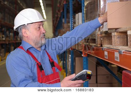 Older A worker with scanner in a factory maintaining stocks of finished products on the shelves in a storeroom.