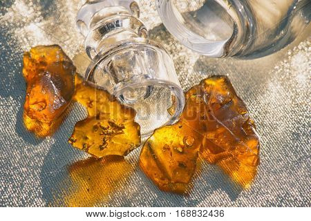 Pieces of cannabis oil concentrate aka shatter with glass rig over sparkling background