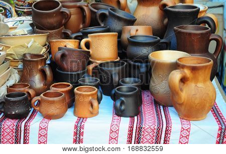 Traditional Ceramic Jugs and cups on Decorative Towel. Showcase of Handmade Ukraine Ceramic Pottery in a Roadside Market with Ceramic Pots and Cups Outdoors.