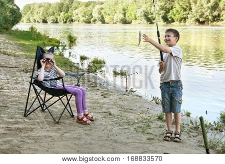 child camping and fishing, people active in nature, boy caught fish on bait, river and forest, summer season