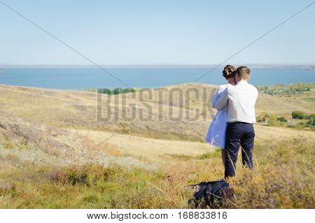Romantic scene. Hugging couple of man and woman looking forward.