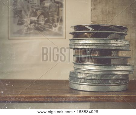 Reels of film are on the shelf in the background of the old movie posters.Stylized photo.