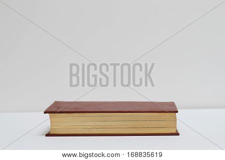 Hardback book on gray cloth. Back to school. Copy space.