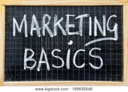 The words Marketing Basics written by hand in white chalk on a blackboard