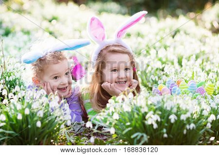 Kids On Easter Egg Hunt In Blooming Spring Garden